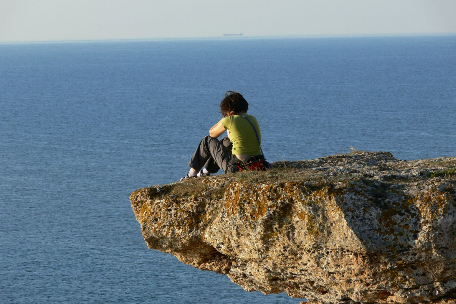 A girl enjoys the sea view from the cliffs