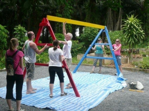 Volunteers constructing a swingset for the kids