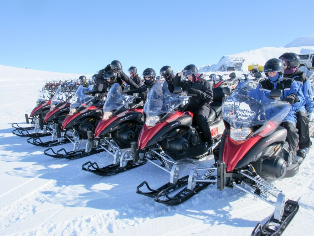 Snowmobiles waiting to set off to explore a glacier on a day trip from Reykjavik, Iceland
