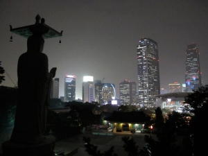 Maitreya Buddha statue with city lights