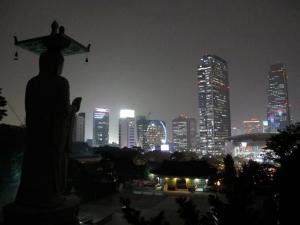 Maitreya Buddha statue with city lights