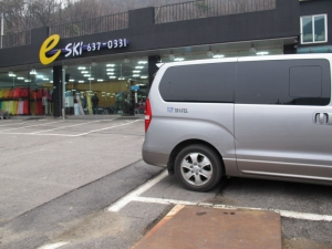 The private van stopping in front of the ski clothes rental shop