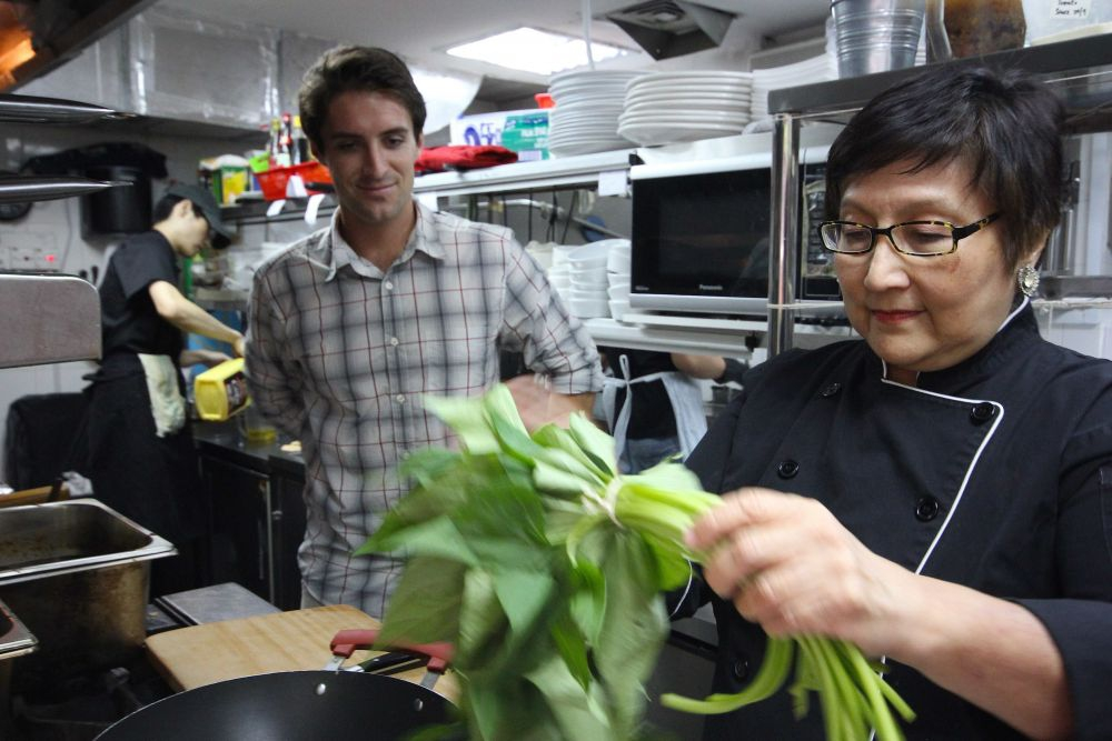 Violet Oon showing Alex how to clean sweet potato leaves