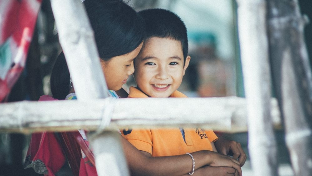 Smiling boy and his older sister at a Fishing Village in Quang Nam, Viet Nam.